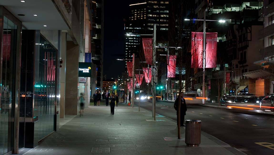 multi-function poles at night with red banners on st georges terrace perth